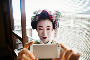 A woman dressed in the traditional geisha style, wearing a kimono and obi, with an elaborate hairstyの写真素材 [FYI02254009]