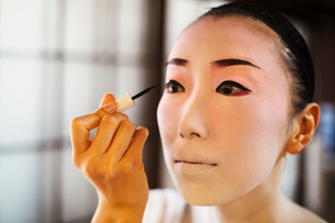 Geisha woman with traditional white face makeup painting on heavy eyeliner with a brush.の写真素材 [FYI02254010]