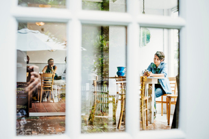 View through a window into a cafe, people sitting at tables.の写真素材 [FYI02254021]