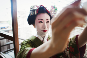 A woman dressed in the traditional geisha style, wearing a kimono and obi, with an elaborate hairstyの写真素材 [FYI02254025]