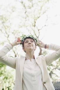 Woman standing in a garden, putting a flower wreath in her hair.の写真素材 [FYI02254026]