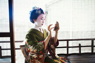 A woman dressed in the traditional geisha style, wearing a kimono and obi, with an elaborate hairstyの写真素材 [FYI02254040]