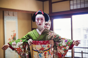 A woman being dressed in the traditional geisha style, wearing a kimono and obi, with an elaborate hの写真素材 [FYI02254045]