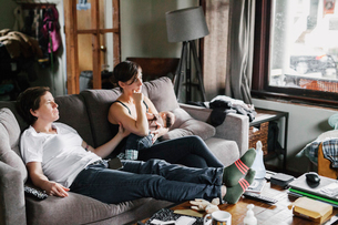 Two women, a couple at home, sitting on the sofa, one breastfeeding a baby.の写真素材 [FYI02254052]