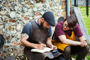 Two men wearing aprons writing into a notebook sat in a garden.の写真素材 [FYI02254060]