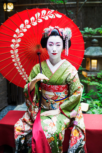 A woman dressed in the traditional geisha style, wearing a kimono and obi, with an elaborate hairstyの写真素材 [FYI02254063]