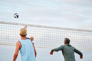 Mature men standing on a beach, playing beach volleyball.の写真素材 [FYI02254065]
