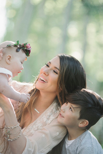 Portrait of a smiling mother, boy and baby girl with a flower wreath on her head.の写真素材 [FYI02254066]