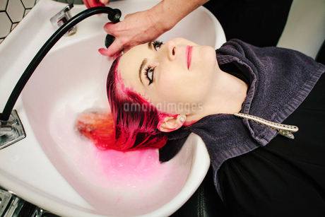 A woman having her hair rinsed with red dye running into the basin.の写真素材 [FYI02254072]
