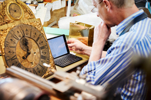 A clock maker in his workshop using a laptop.の写真素材 [FYI02254084]