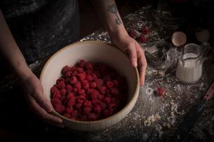 Valentine's Day baking. A woman preparing raspberries in a bowl.の写真素材 [FYI02254085]