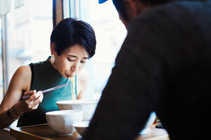A ramen noodle cafe in a city.  A man and woman seated eating noodles from large white bowls.の写真素材 [FYI02254115]