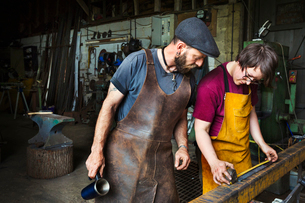 Two blacksmiths measure a length of metal in a workshop.の写真素材 [FYI02254116]