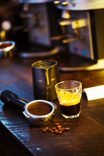 Specialist coffee shop. A coffee machine grounds holder, a heap of coffee beans and a glass cup withの写真素材 [FYI02254122]