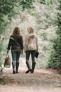 Two women walking in coats and boots along a country path with a basket.の写真素材 [FYI02254133]