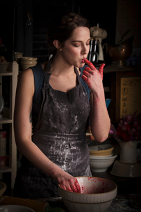 Valentine's Day baking, young woman standing in a kitchen, preparing raspberry jam, licking her fingの写真素材 [FYI02254142]