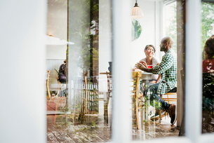 View through a window into a cafe, people sitting at tables.の写真素材 [FYI02254149]