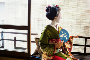 A woman dressed in the traditional geisha style, wearing a kimono and obi, with an elaborate hairstyの写真素材 [FYI02254157]
