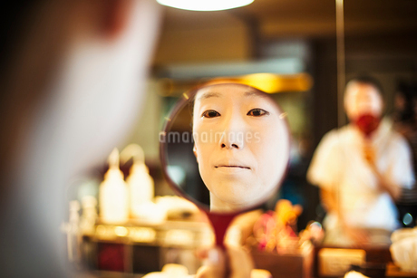 A modern geisha or maiko woman being prepared in traditional fashion, with white face makeup.の写真素材 [FYI02254160]