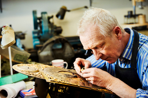 A clock maker busy in his workshop.の写真素材 [FYI02254161]