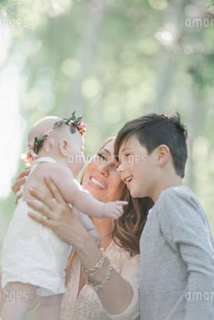 Portrait of a smiling mother, boy and baby girl with a flower wreath on her head.の写真素材 [FYI02254165]