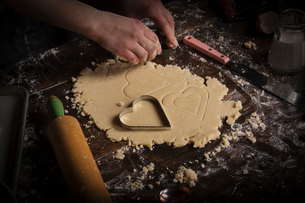 Valentine's Day baking. Woman cutting out heart shaped biscuits from dough on a floured surface.の写真素材 [FYI02254172]