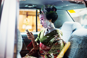 A woman dressed in the traditional geisha style, wearing a kimono and obi, with an elaborate hairstyの写真素材 [FYI02254175]