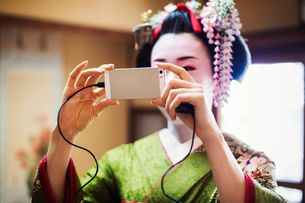 A woman dressed in the traditional geisha style, wearing a kimono and obi, with an elaborate hairstyの写真素材 [FYI02254183]