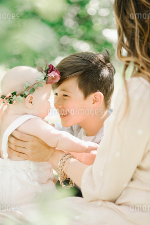 A woman, a boy and baby girl with a flower wreath on her head, sitting in a garden.の写真素材 [FYI02254238]