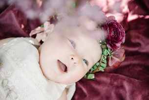 Portrait of a smiling baby girl with a flower wreath on her head.の写真素材 [FYI02254242]