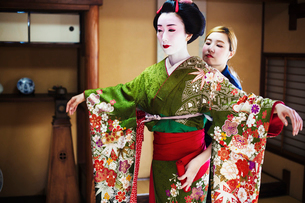A woman being dressed in the traditional geisha style, wearing a kimono and obi, with an elaborate hの写真素材 [FYI02254286]