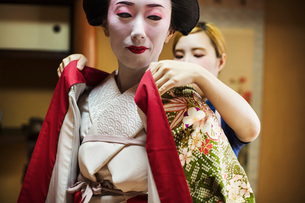 A woman being dressed in the traditional geisha style, wearing a kimono with white face makeup withの写真素材 [FYI02254287]