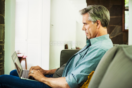 A man seated on a sofa, using a laptop.の写真素材 [FYI02254290]