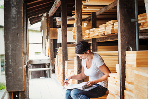 Woman sitting in a lumber yard, holding a folder.の写真素材 [FYI02254303]