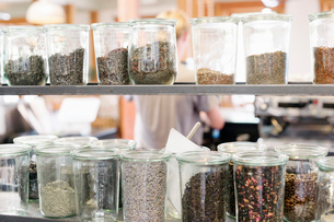 A selection of dried foods and condiments in glass jars on shelves in a coffee shop.の写真素材 [FYI02254317]