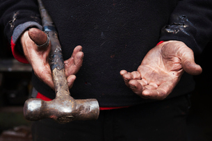 Close up of a blacksmith's hands, holding a metal hammer.の写真素材 [FYI02254320]