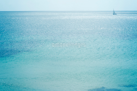 Distant sailing boat on a shimmering blue sea.の写真素材 [FYI02254322]