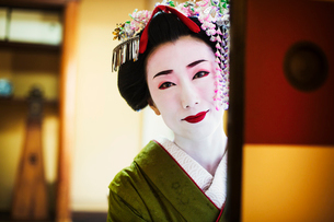 A woman dressed in the traditional geisha style, wearing a kimono and obi, with an elaborate hairstyの写真素材 [FYI02254324]