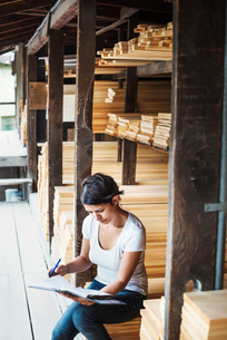 Woman sitting in a lumber yard, holding a folder.の写真素材 [FYI02254337]