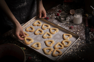 Valentine's Day baking, woman arranging heart shaped biscuits on a baking tray.の写真素材 [FYI02254355]