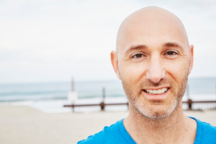 Bald mature man standing on a beach, smiling at camera.の写真素材 [FYI02254379]