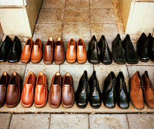 Rows of black and brown leather shoes standing on the front steps of a building.の写真素材 [FYI02254380]