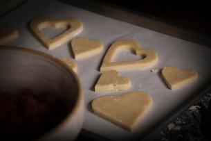 Valentine's Day baking, high angle view of heart shaped biscuits on a baking tray.の写真素材 [FYI02254412]