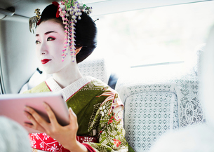 A woman dressed in the traditional geisha style, wearing a kimono with an elaborate hairstyle and flの写真素材 [FYI02254422]