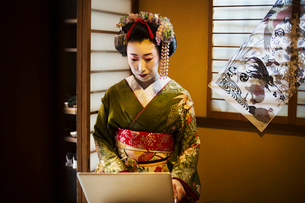 A woman dressed in the traditional geisha style, wearing a kimono and obi, with an elaborate hairstyの写真素材 [FYI02254425]