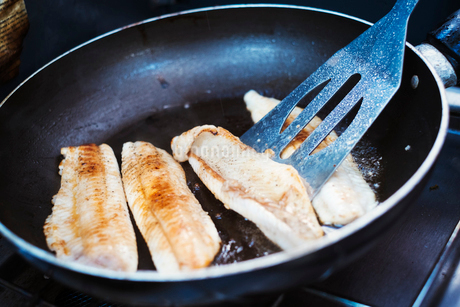 Close up of fish fillets being fried in a frying pan.の写真素材 [FYI02254428]
