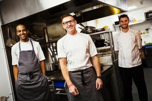 Portrait of three chefs standing in a restaurant kitchen.の写真素材 [FYI02254449]