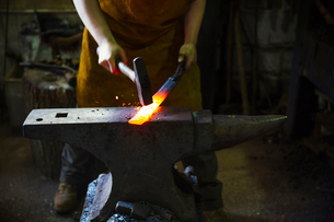 A blacksmith strikes a length of red hot metal on an anvil with a hammer in a workshop.の写真素材 [FYI02254453]