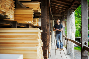 Man standing in a lumber yard, holding a folder, writing notes.の写真素材 [FYI02254460]