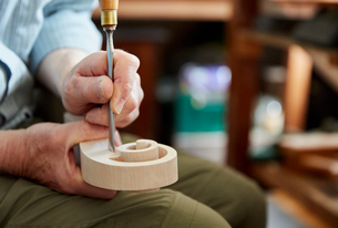 A violin maker using hand tools to smooth and finish a new wooden violin headstock, curled scroll ofの写真素材 [FYI02254463]